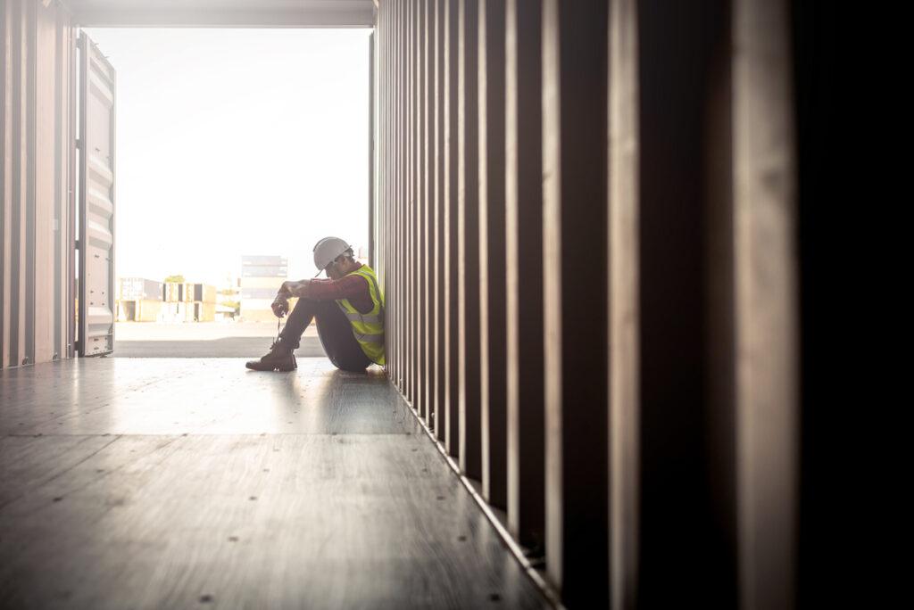 mobbing am arbeitsplatz Stressed despair staff in logistic business sittng in container box at shipyard